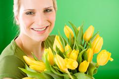 Young happy woman hold yellow tulips flower Stock Photos