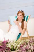 summer terrace red hair woman relax in deckchair - stock photo