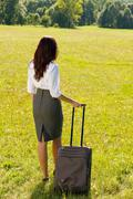 businesswoman sunny meadow leaving with luggage - stock photo
