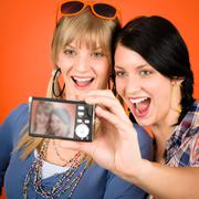 Stock Photo of two young woman friends taking picture smiling