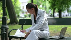 Busy multitasking businesswoman working in city park Stock Footage