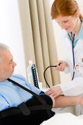 hospital - doctor check blood pressure patient - stock photo