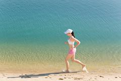 Summer sport fit woman jogging along seashore Stock Photos