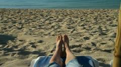 Feet on a sunbed by a beach Stock Footage