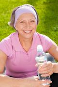 Stock Photo of senior sportive woman smile hold bottle water