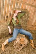provocative position young cowgirl on hay - stock photo