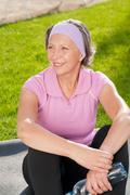 senior sportive woman sitting on mat sunny - stock photo