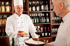 chef cook with tapas on tray restaurant - stock photo