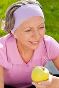 Senior sportive woman smile eat apple outdoor Stock Photos