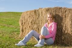 sportive young woman relax by bales sunset - stock photo