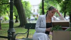 Just fired, unemployed sad young businesswoman talking on cellphone in the park Stock Footage