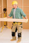 Handyman carpenter mature carry wooden beam Stock Photos