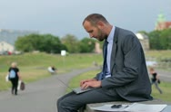 Businessman working on laptop in the city Stock Footage