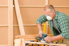 Stock Photo of handyman sanding wooden board diy home renovation