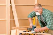 Handyman sanding wooden board diy home renovation Stock Photos
