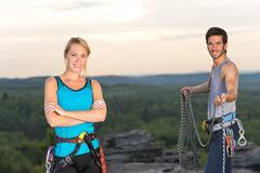Rock climbing active people on top sunset Stock Photos