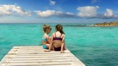 Little sisters girls looking idyllic landscape in formentera beach Stock Footage