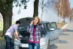 car breakdown couple calling for road assistance - stock photo