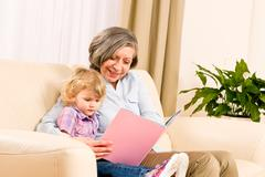 Grandmother and granddaughter read book together Stock Photos