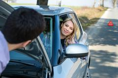 Car troubles man help woman defect vehicle Stock Photos