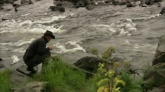 A man getting water from a river Stock Footage