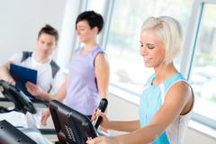 Fitness young people on treadmill cardio workout Stock Photos