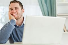 Stock Photo of Businessman smiling tired in his homeoffice