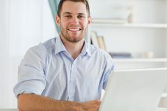 Smiling businessman with rolled up sleeves in his homebusiness - stock photo