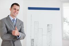 Businessman giving thumb up next to diagram Stock Photos
