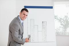 Stock Photo of Smiling businessman editing column graph