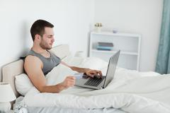 Handsome man purchasing online - stock photo