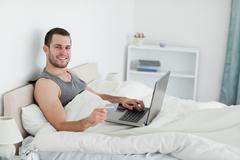 Smiling man purchasing online - stock photo