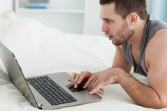 Stock Photo of Man using a laptop while lying on his belly