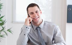 Businessman getting pleasant news on the mobile phone - stock photo