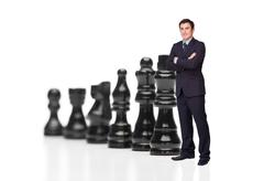 Stock Photo of Businessman in front of black chess pieces