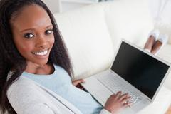 Stock Photo of Woman on couch with her laptop