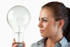 Businesswoman looking at huge light bulb in her hand - stock photo