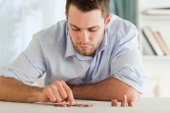 Businessman counting his small change - stock photo