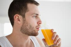 Stock Photo of Close up of a healthy man drinking orange juice