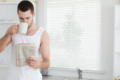 Man drinking tea while reading the news Stock Photos