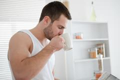 Stock Photo of Man drinking coffee while reading the news
