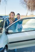 Pushing car technical failure two young women Stock Photos