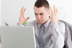 Stock Photo of Close up of businessman experiencing problems with his laptop