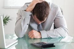 Close up of businessman unhappy about his calculations - stock photo