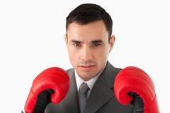 Close up of businessman wearing boxing gloves - stock photo