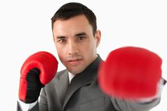Close up of businessman with boxing gloves slamming - stock photo