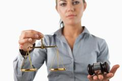 Scale and gavel being held by female lawyer Stock Photos