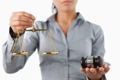 Gavel and scale being held by female lawyer Stock Photos