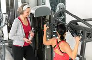 Stock Photo of personal trainer at fitness center showing exercise