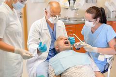 Vanhempi mies hammaslääkärit leikkaus on toimintaa Kuvituskuvat